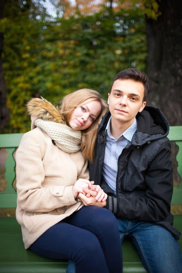Junge und Mädchen, die, sitzend auf der Bank umarmt und küsst lizenzfreie stockfotos