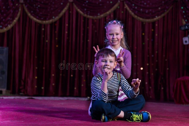 Junge und Mädchen, die zusammen auf Stadium sitzen lizenzfreies stockfoto