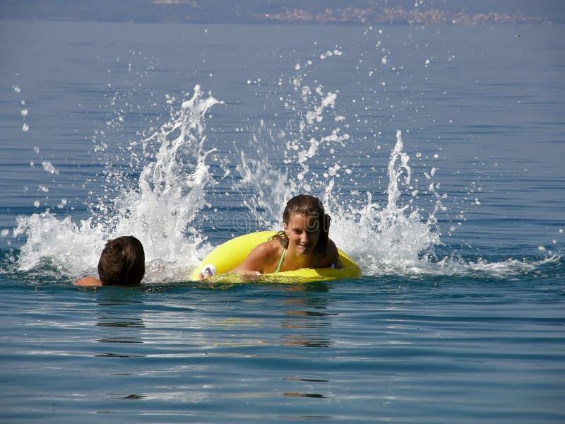 Junge und Mädchen haben ein Rennen in Meer stockfoto