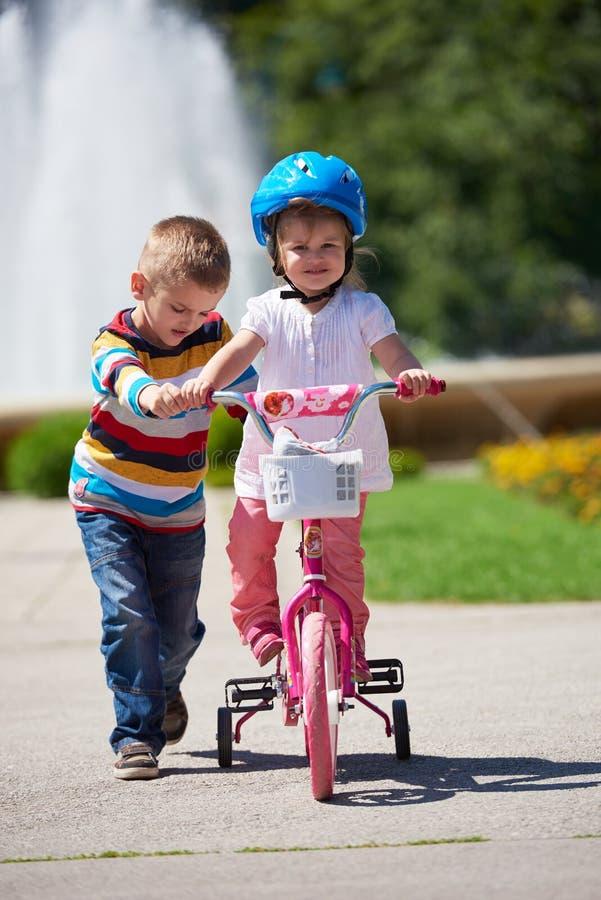 Junge und Mädchen im Park lernend, ein Fahrrad zu reiten lizenzfreies stockfoto