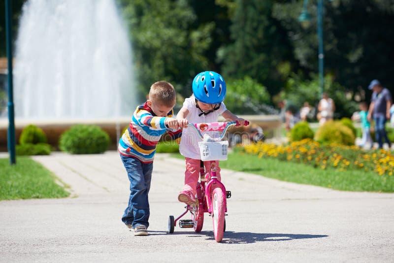 Junge und Mädchen im Park lernend, ein Fahrrad zu reiten lizenzfreie stockfotos