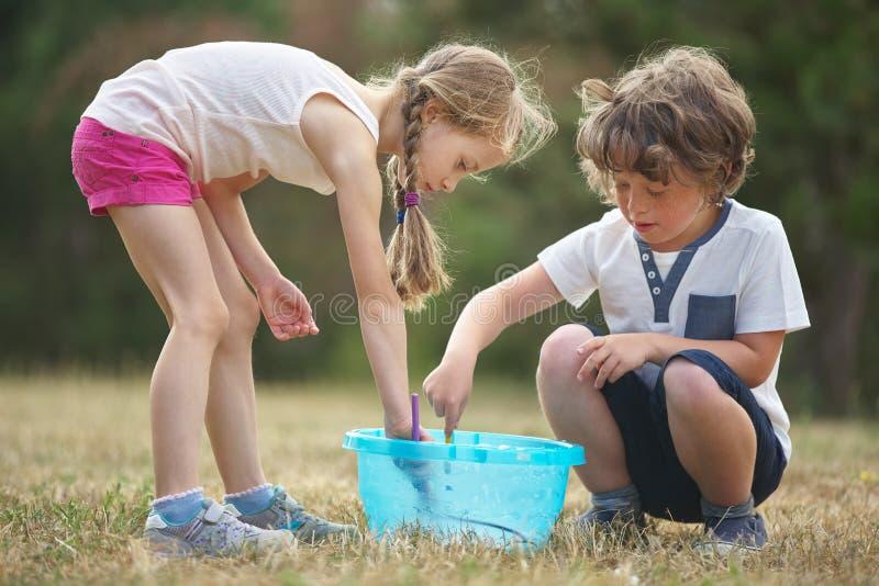 Junge und Mädchen machen Seifenblasen stockfotos