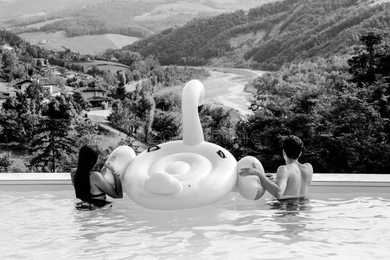 Junge und Mädchen mit aufblasbarem Flamingo zurück in einem Pool stockbild