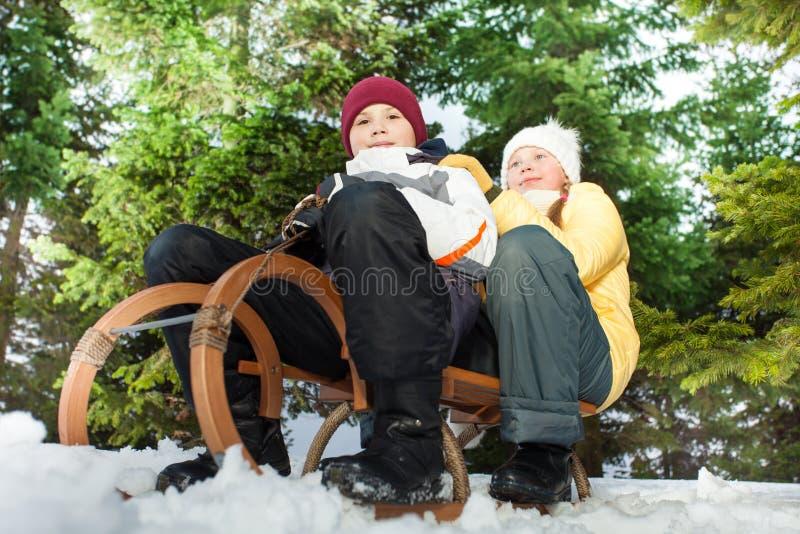 Junge und Mädchen schieben unten einen Hügel auf hölzernem Schlitten lizenzfreie stockbilder