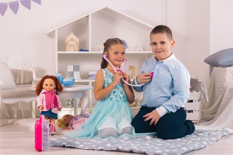Junge Junge und Mädchen spielen Arzt und Patientin, Mädchen hört Herzschlag mit Stethoskop stockfoto