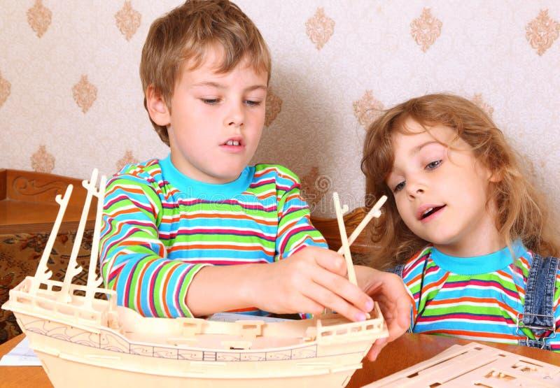 Junge und Mädchen stellen selbst gemachtes hölzernes Boot her lizenzfreie stockfotografie