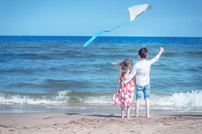 Junge und Mädchen am Strand mit einem Drachen Freiheit, sorgloses childho stockbild