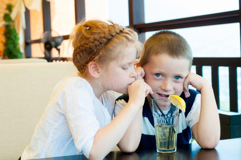 Junge und Mädchen trinken ein Getränk stockfotografie