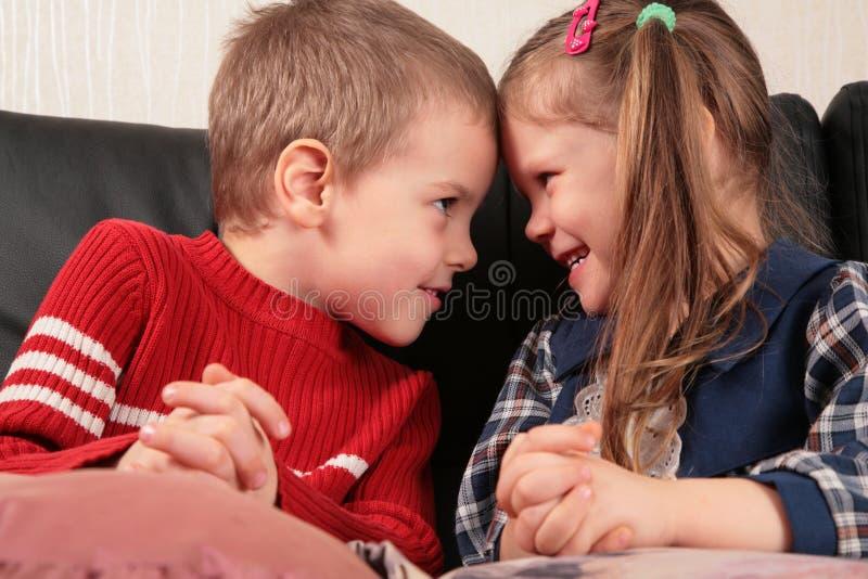 Junge und Mädchen vertraulich auf Sofa lizenzfreies stockfoto