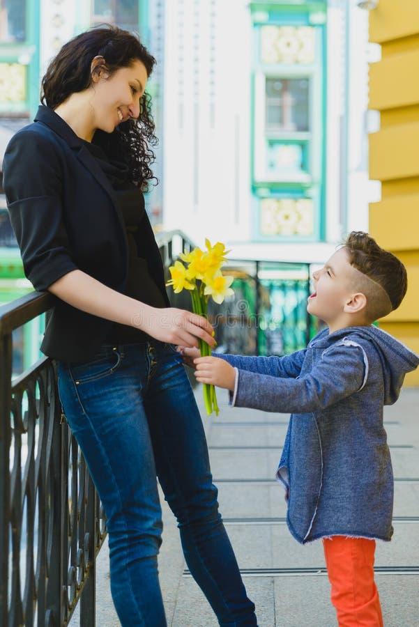 Junge und Mutter an der Stadt, an der Blume und am Geschenk Muttertagesfeierkonzept lizenzfreie stockfotos