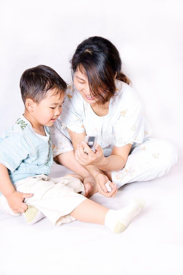 Junge und Mutter, die Handy betrachten stockfotografie