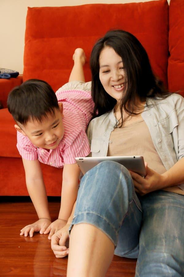 Junge und Mutter, die Spiele mit Tablette spielen lizenzfreie stockbilder