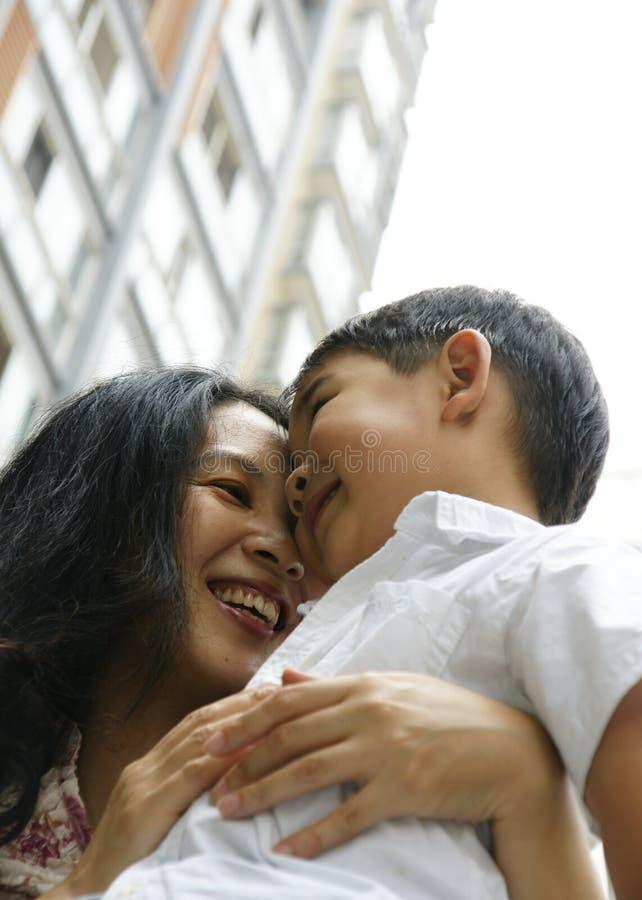 Junge und Mutter, die umarmen und lächeln stockfoto