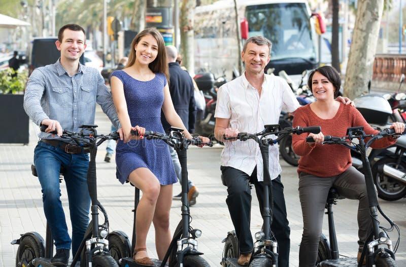 Junge und reife Paare, die mit den Fahrrädern im Freien bleiben lizenzfreie stockfotografie