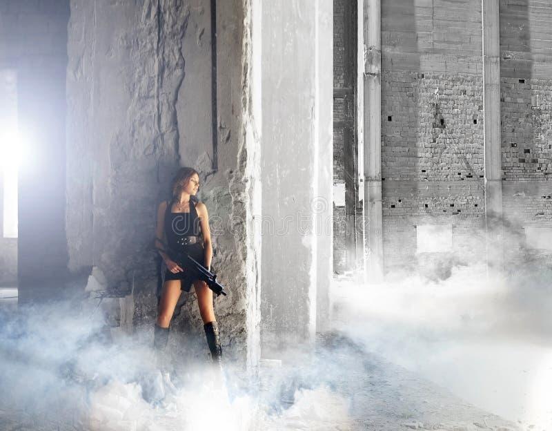 Junge und reizvolle Frau mit einem Maschinengewehr stockfoto