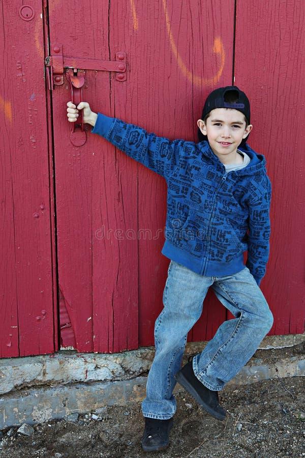Junge und rote Tür lizenzfreies stockbild