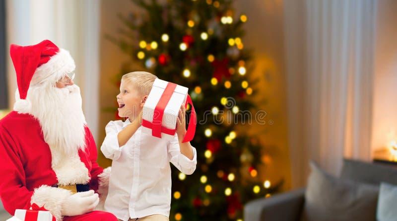 Junge und Sankt mit Weihnachtsgeschenken zu Hause lizenzfreie stockfotos
