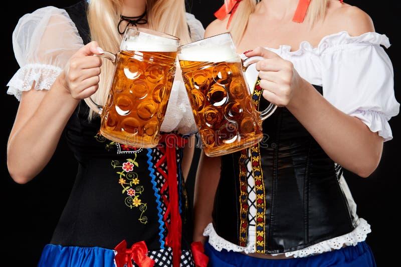 Junge und schöne bayerische Mädchen mit zwei Bierkrügen auf schwarzem Hintergrund stockfotografie