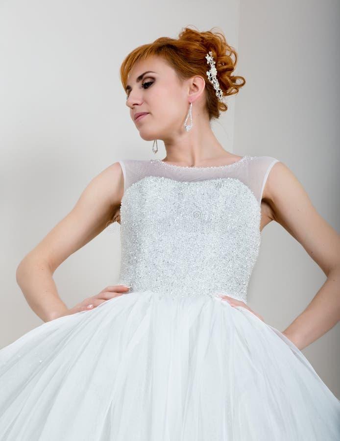 Junge und schöne Rothaarigebraut kleidete das Hochzeitskleid, das im Studio aufwirft stockfoto