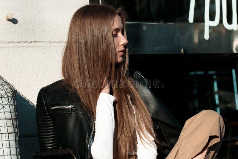 Junge und Schönheit sitzt auf einer Bank in der Straße und wirft für die Kamera auf stockfotos