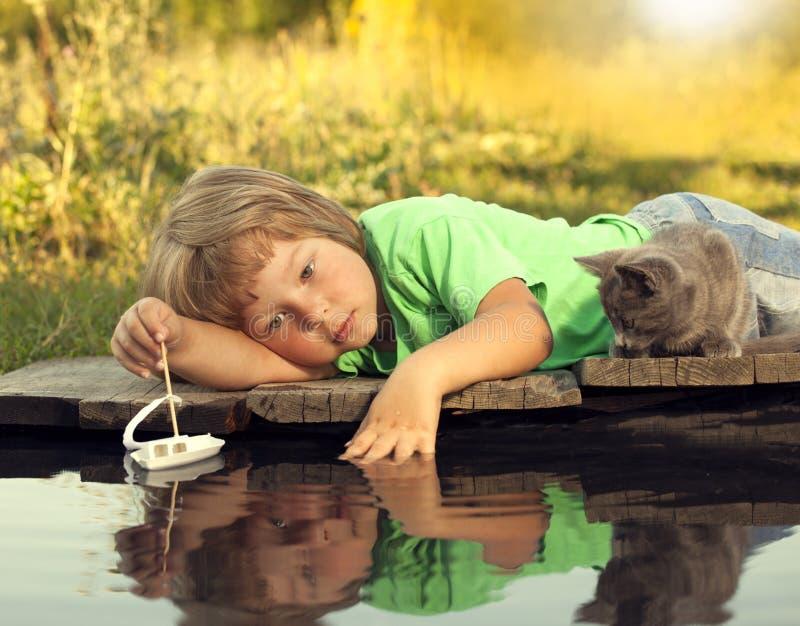 Junge und sein geliebtes Kätzchen, die mit einem Boot vom Pier im Teich spielen stockfotografie