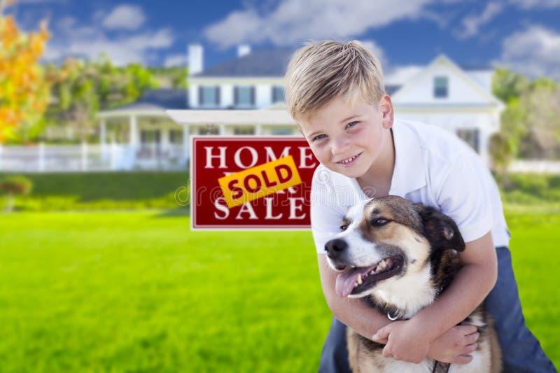Junge und sein Hund vor Verkaufszeichen, Haus stockbilder