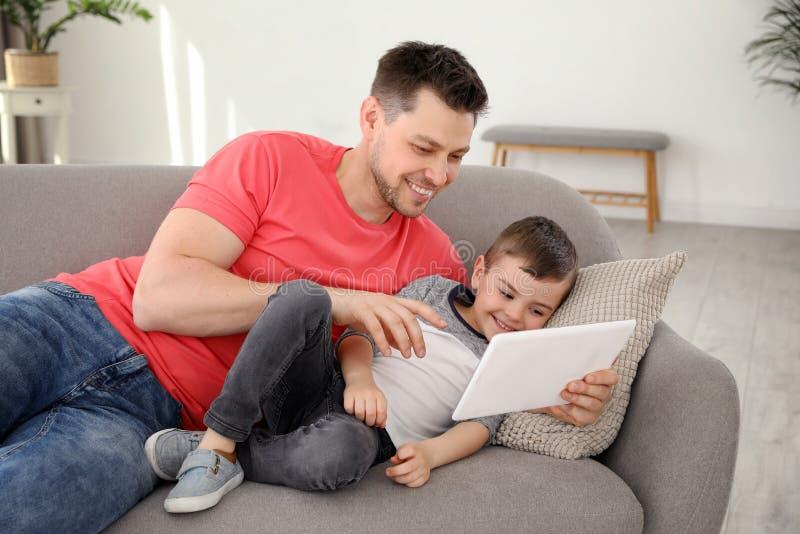 Junge und sein Vater mit der Tablette, die zu Hause auf Sofa liegt stockbild