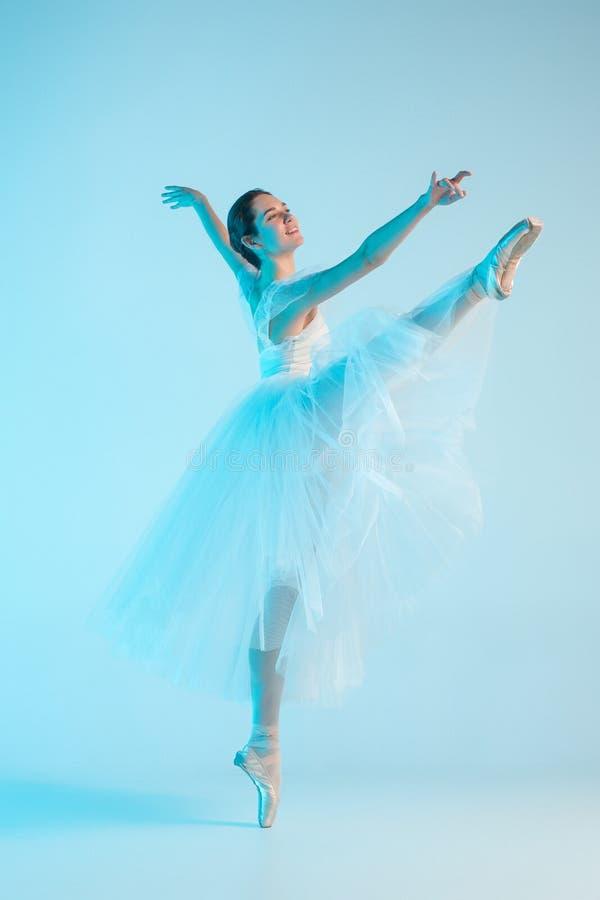 Junge und unglaublich schöne Ballerina tanzt in ein blaues Studio lizenzfreies stockfoto