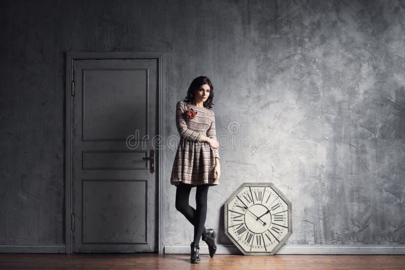 Junge und würdevolle Frau, die in einem alten Innenraum aufwirft stockbilder