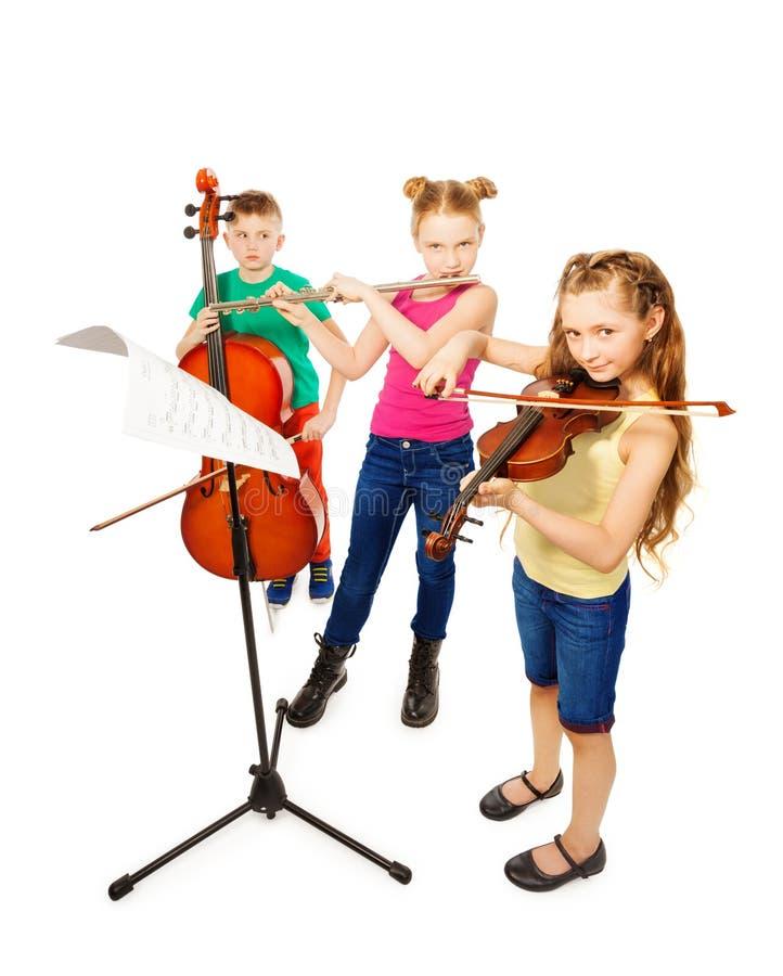 Junge und zwei Mädchen, die auf Musikinstrumenten spielen lizenzfreie stockfotografie
