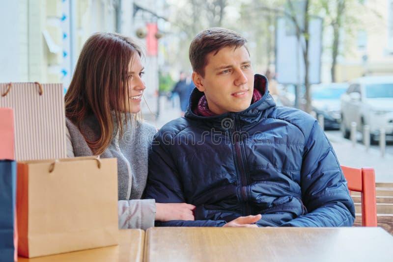 Junge Unterhaltungspaare mit Einkaufstaschen im Straßencafé, in WarteTasse Kaffee und im Tee stockfotos