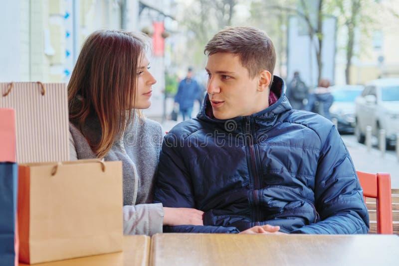 Junge Unterhaltungspaare mit Einkaufstaschen im Stra?encaf?, in WarteTasse Kaffee und im Tee stockfotos