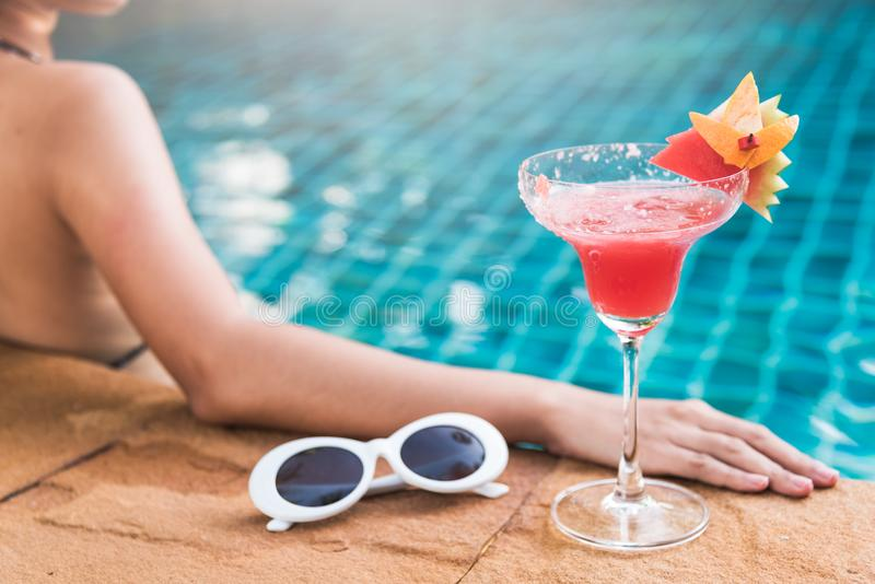 Junge unterstützen Frau im BikiniSwimmingpool-Getränkcocktail, stockbild