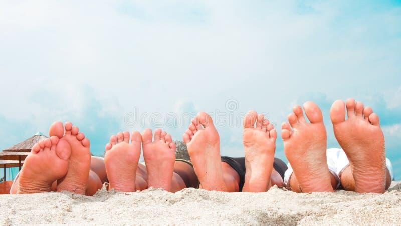 Junge verbinden Füße am Strand stockfotografie