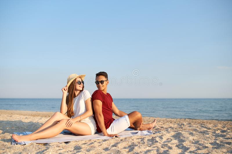 Junge verschiedene Rennpaare, die zur?ck zu R?ckseite auf Badetuch am tropischen Reisestandort sitzen Liebhaber an der sch?nen Se stockfoto