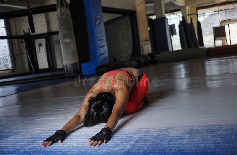 Junge verschwitzte Asiatin im Sport kleidet ausdehnen zurück und Rückenflosse auf Turnhalle Dojoboden im harten Trainingstraining lizenzfreie stockbilder