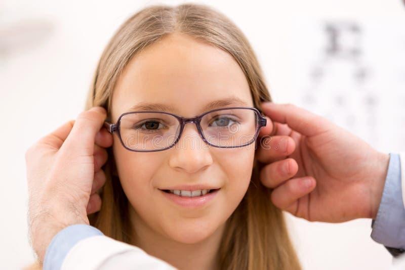 Junge versuchende Gläser des kleinen Mädchens am Optiker lizenzfreie stockfotografie