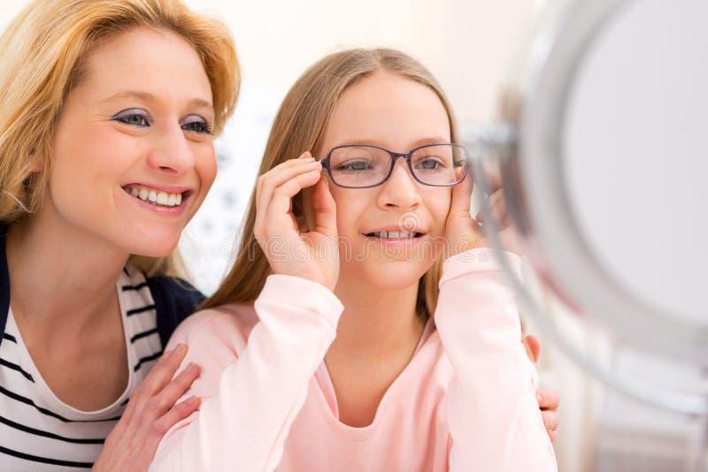 Junge versuchende Gläser des kleinen Mädchens am Optiker w ihre Mutter lizenzfreies stockbild