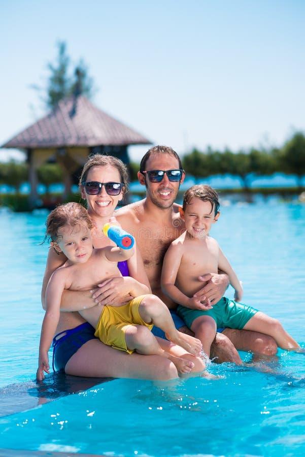 Junge vierköpfige Familie auf tropischem Strand des weißen Sandes lizenzfreies stockfoto