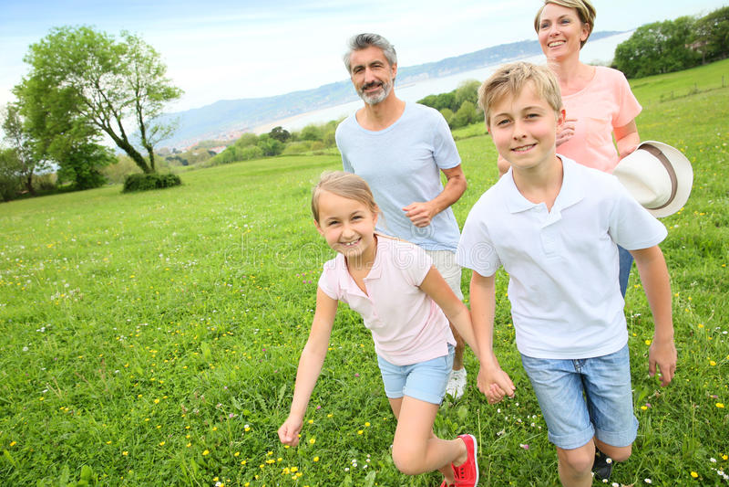 Junge vierköpfige Familie, die auf grünem Gras läuft stockfotografie
