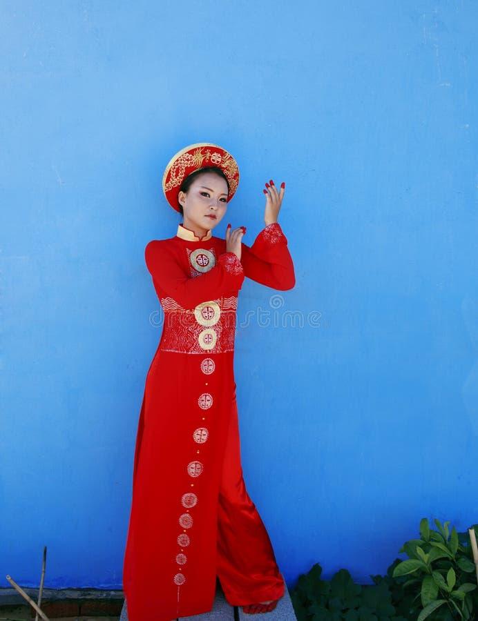 Junge vietnamesische Frau der Schönheit im roten Staatsangehörigen lizenzfreie stockfotos