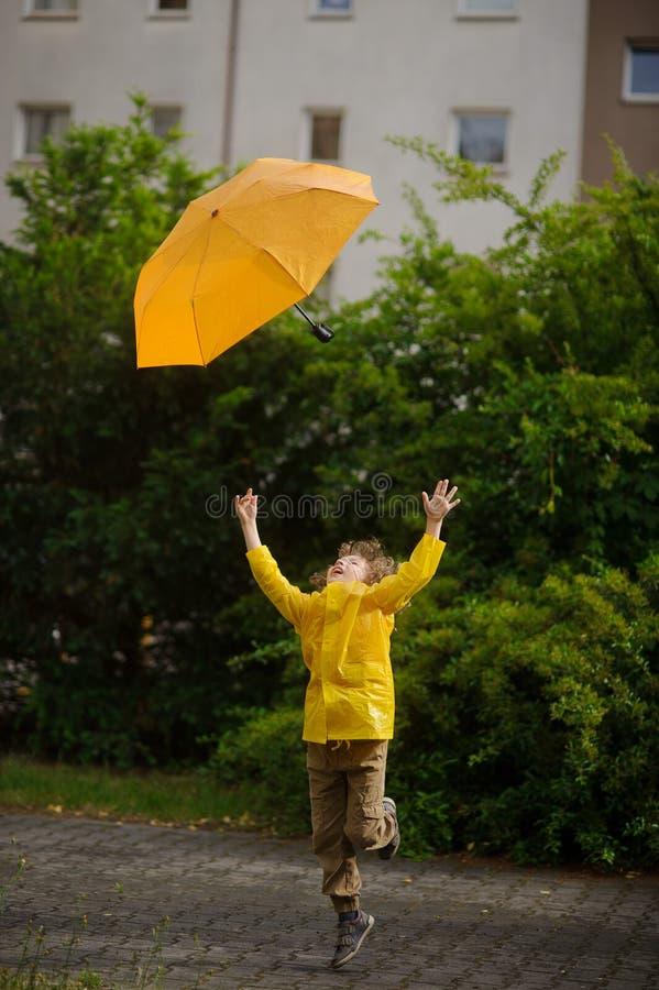 Junge von 8-9 Jahren in einem hellen gelben Regenmantel versucht, den Abreiseregenschirm zu fangen stockbild