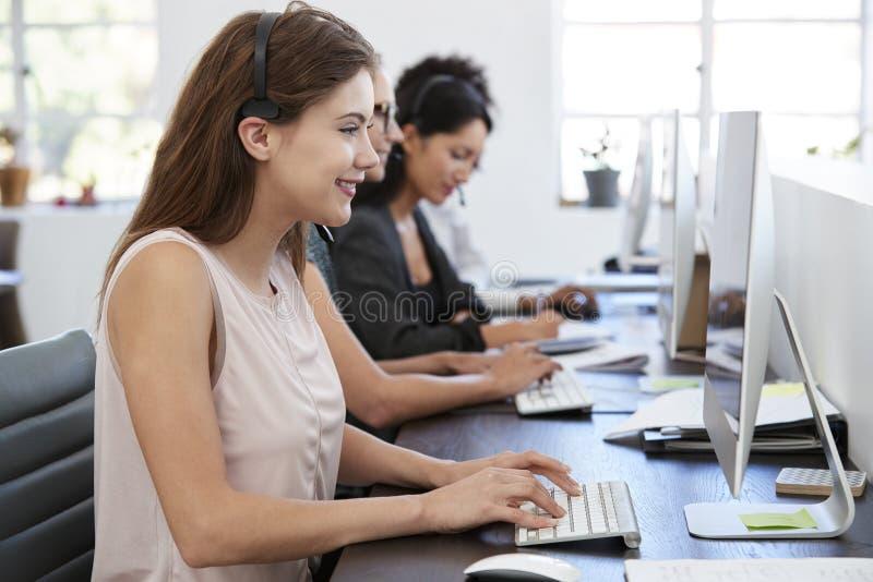 Junge weiße Frau, die am Computer im Büro mit Kopfhörer arbeitet stockfotos