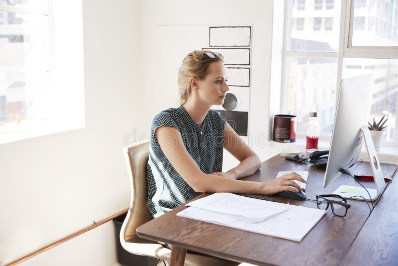 Junge weiße Frau, die in einem Büro unter Verwendung eines Computers arbeitet stockbild