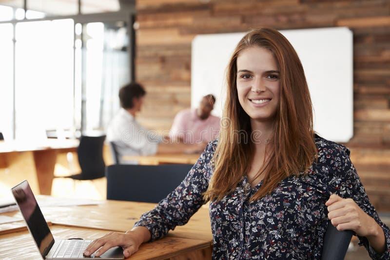 Junge weiße Frau mit dem langen roten Haar, das im Büro sitzt stockfotos