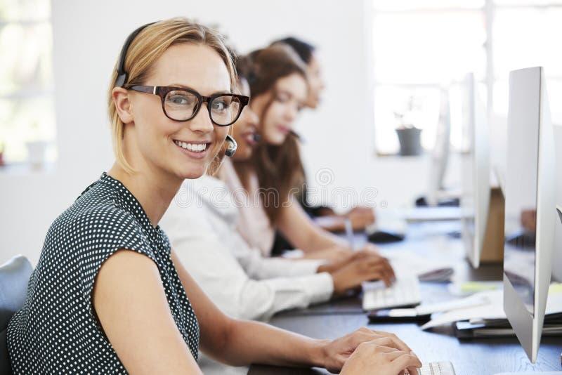 Junge weiße Frau mit Kopfhörer lächelnd zur Kamera im Büro lizenzfreie stockfotos