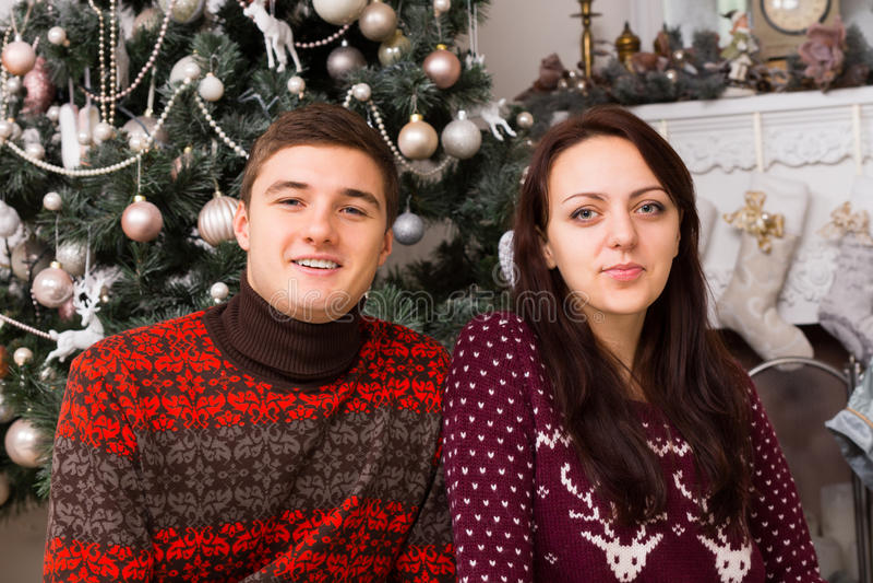 Junge weiße Paare in Front Christmas Tree lizenzfreies stockfoto
