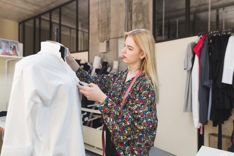 Junge weibliche Damenschneiderin steht in einem manikürten Studio und justiert Kleidung lizenzfreies stockbild