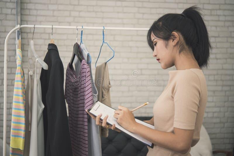 Junge weibliche Designermode, die für Näherinkleid arbeitet stockfotos