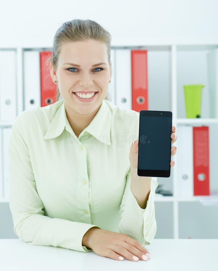 Junge weibliche Geschäftsfrau, die in der Hand den Smartphone sitzt im Büro zeigt stockbild
